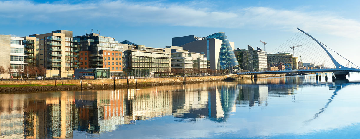 Modern buildings and offices on Liffey river in Dublin bridge on the right is a famous Harp bridge