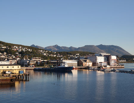 Buildings by the water with mountains in background, Harstad