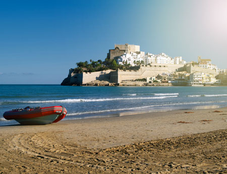 Rubber boat on the beach against Peniscola castle, Spain