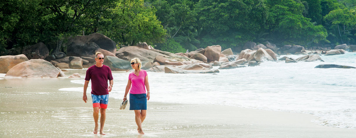 Couple walking along the beach in Praslin Island