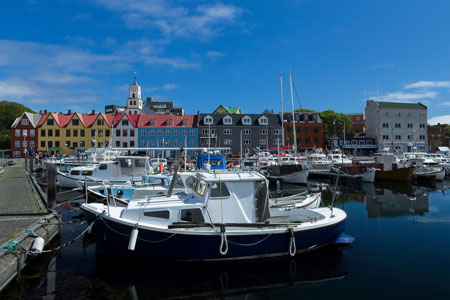 Boats in Marina Torshavn with colouful buildings and church