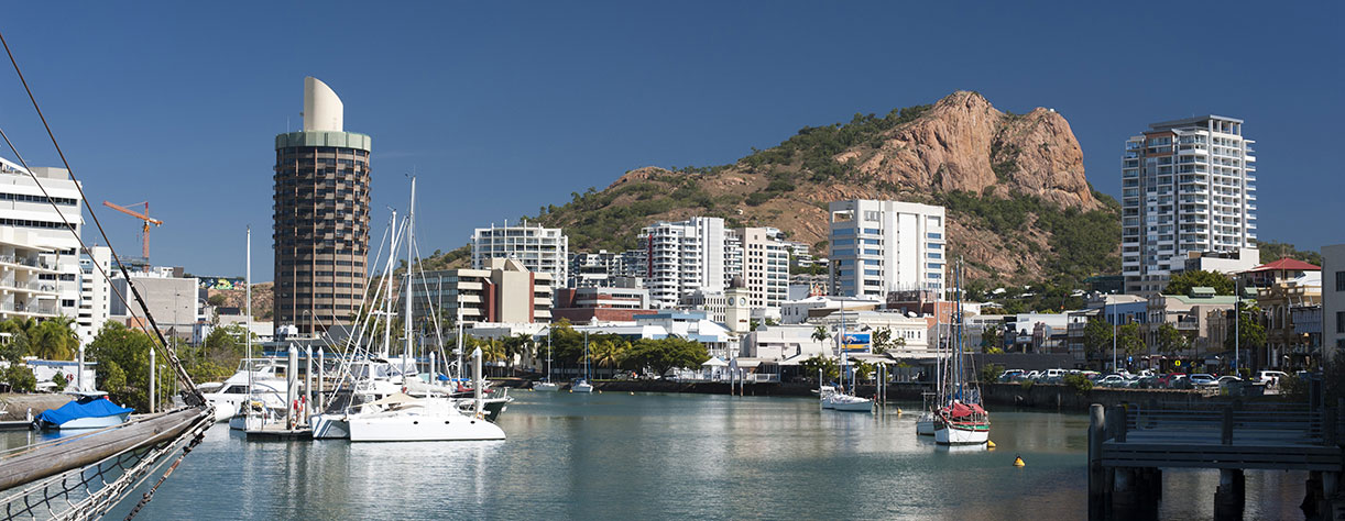 View down the quay of boats moored in the calm water of Townsville marina in Queensland, Australia with modern waterfront city central architecture and a castle hill behind
