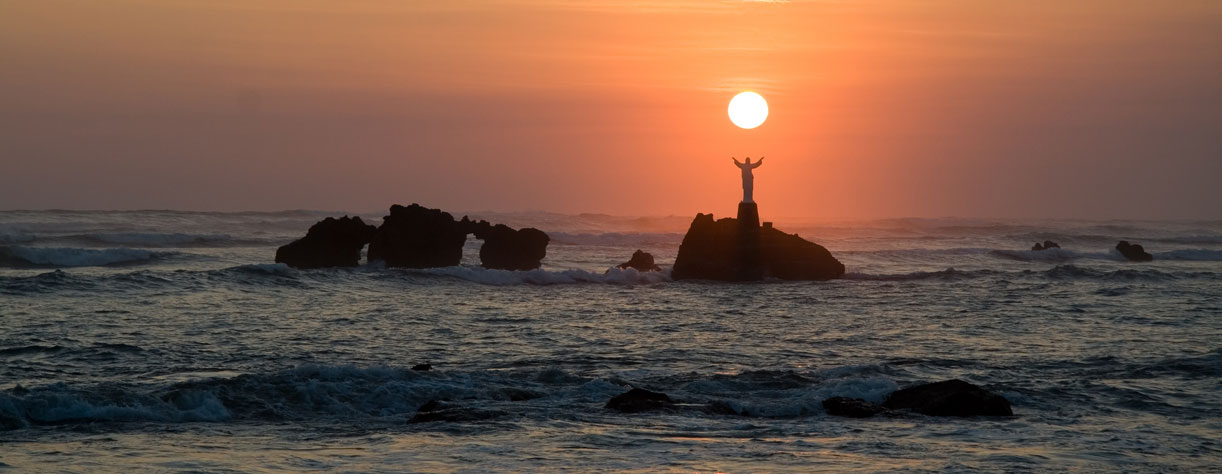 The sun sets over a statue of Jesus out in the ocean in El Salvador