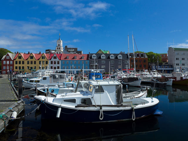 Boats in marina Torshavn Faroe Islands with colorful buildings and church in the background