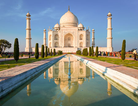 Taj Mahal on a bright and clear day at sunset reflects in the pond