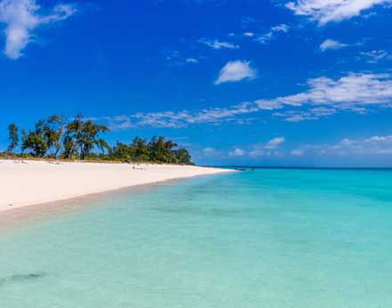 Idyllic tropical beach with white sand turquoise ocean water and blue sky
