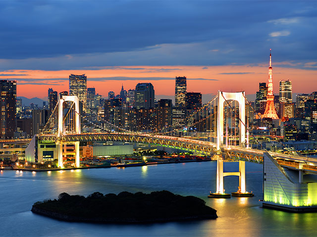 Rainbow Bridge spanning Tokyo Bay with Tokyo Tower visible in the background