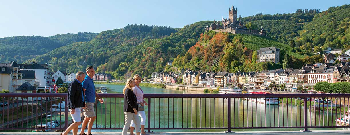 Friends walking across bridge in Cochem with Reichsburg Castle in the background, Germany