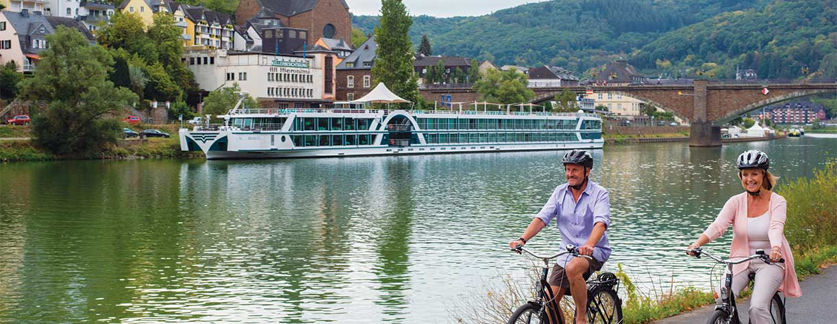 Couple cycling in Cochem, Germany with Brabant in the background