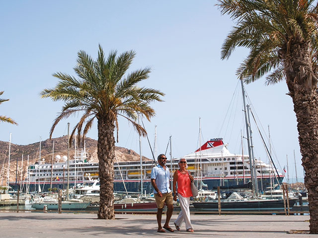 Couple walking along in Cartagena, Spain - Braemar in the background