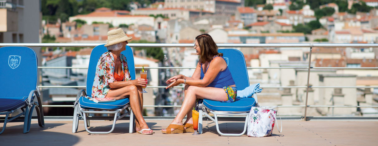 Ladies on deck, talking on sun loungers
