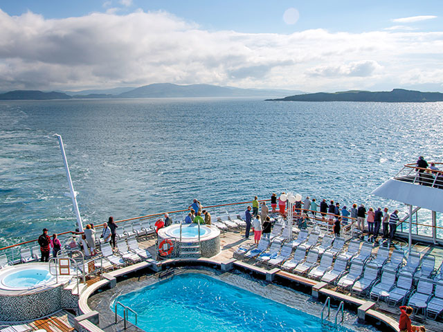 Balmoral cruising, guests enjoying swiming pool on deck