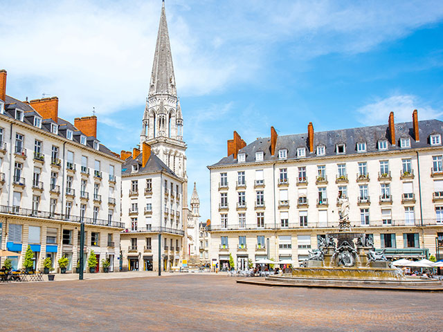 View on Royal square with fountain and church tower, Nantes, France