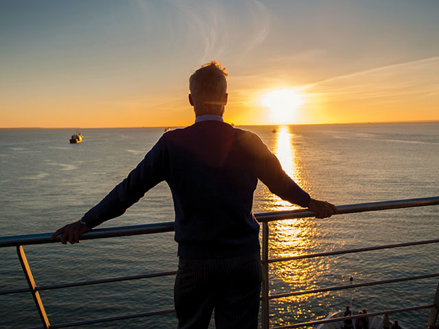 Man looking out to sea from on board